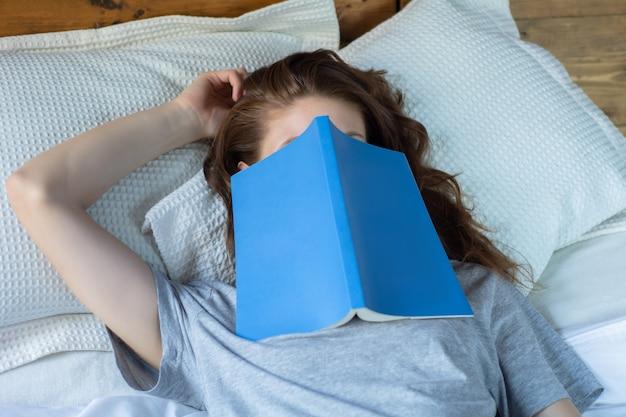 Jonge vrouwenslaap op bed met boek