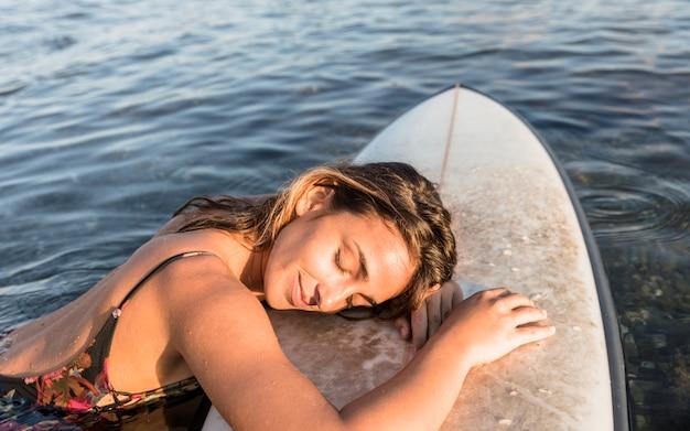 Jonge vrouwenslaap op surfplank