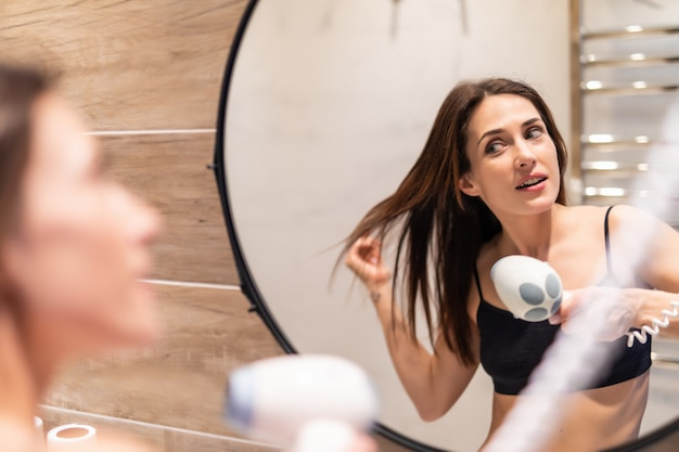 Jonge vrouwenslag die haar haar in badkamers drogen