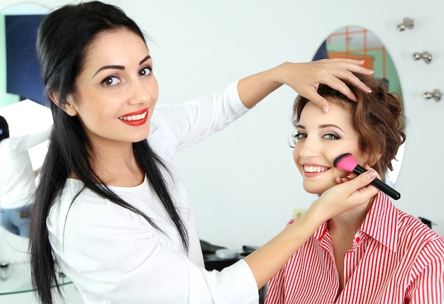 Jonge vrouwenstylist die make-up mooi meisje in schoonheidssalon doet