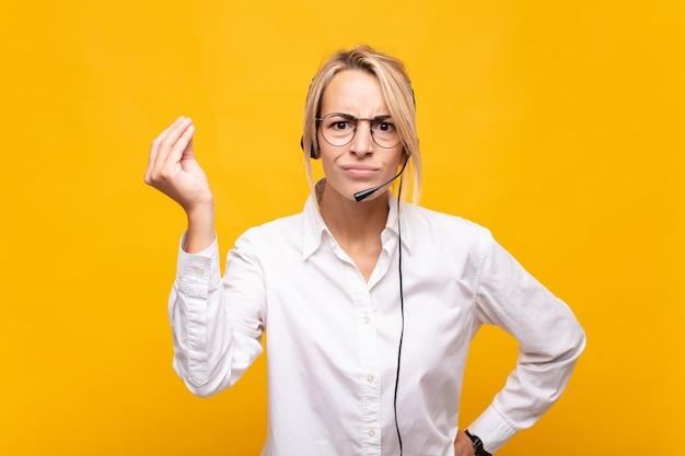 Jonge vrouwentelemarketeer die capice of geldgebaar maakt, u vertelt om uw schulden te betalen!