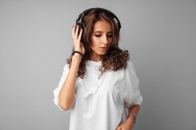 Jonge vrouwentiener die aan muziek met haar hoofdtelefoons luistert