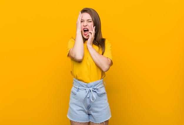 Jonge vrouwentiener die een geel en overhemd draagt dat troosteloos jammert