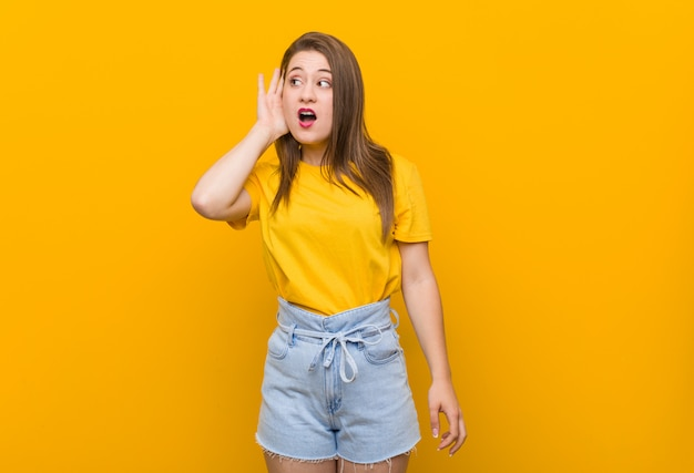 Jonge vrouwentiener die een geel overhemd draagt dat aan een roddel probeert te luisteren.