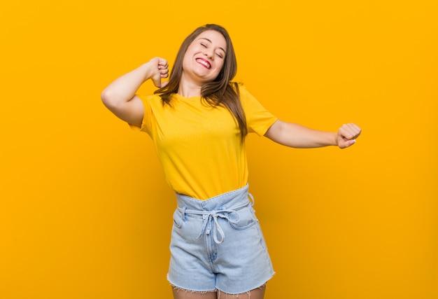 Jonge vrouwentiener die een geel overhemd draagt dat en pret danst heeft.