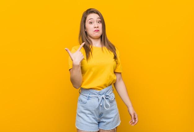 Jonge vrouwentiener die een geel overhemd draagt dat met vinger op u richt alsof uitnodigend dichterbij kom.