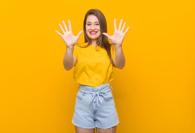 Jonge vrouwentiener die een geel overhemd draagt dat nummer tien met handen toont.