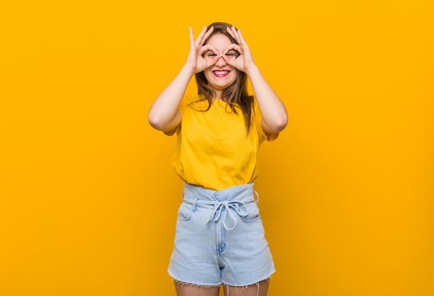 Jonge vrouwentiener die een geel overhemd draagt dat ok teken over ogen toont