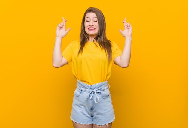 Jonge vrouwentiener die een geel overhemd draagt dat vingers kruist voor het hebben van geluk