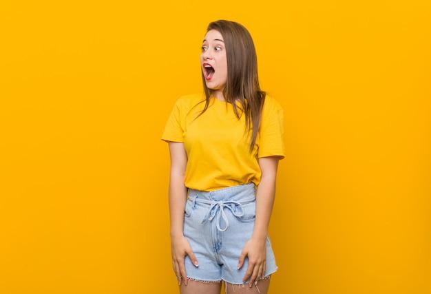 Jonge vrouwentiener die een geel overhemd draagt dat wordt geschokt wegens iets dat zij heeft gezien.