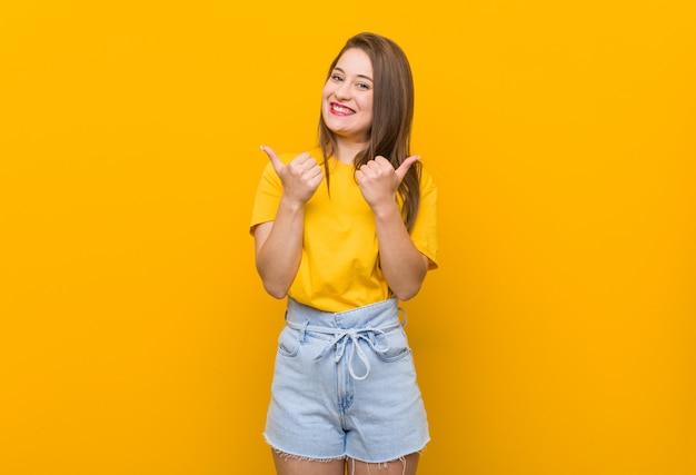 Jonge vrouwentiener die een geel overhemd draagt die beide duimen omhoog, glimlachend en zeker opheft.