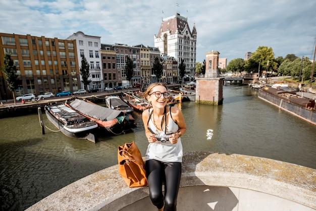 Jonge vrouwentoerist die dichtbij de oude haven in de stad rotterdam, nederland reizen