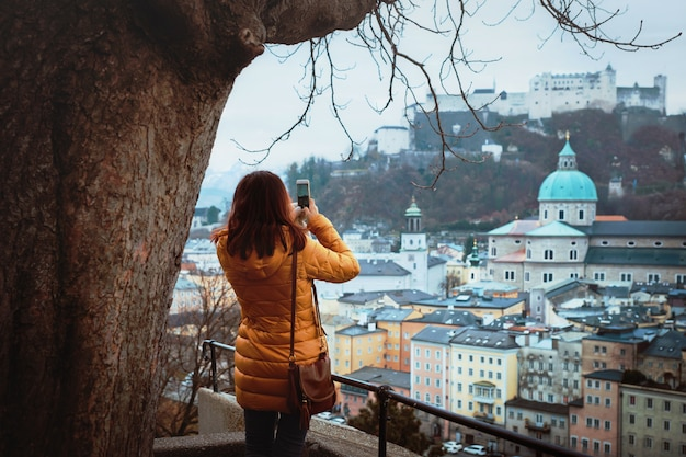 Jonge vrouwentoerist die foto op een telefoon van een panorama van de middeleeuwse stad salzburg neemt