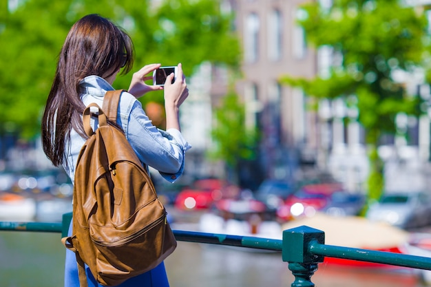 Jonge vrouwentoerist die foto op mooi uitzicht van europese stad met mobiele smartphonecamera nemen