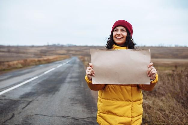 Jonge vrouwentoerist die gele jas en rode hoed draagt, staat met een blanco posterpapier aan de kant van een lege winterweg.