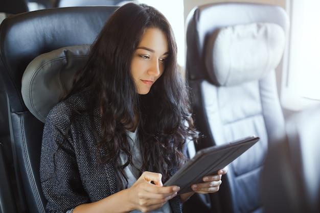 Jonge vrouwentoerist die haar tabletcomputer gebruikt tijdens het reizen met de trein. reisapplicatie
