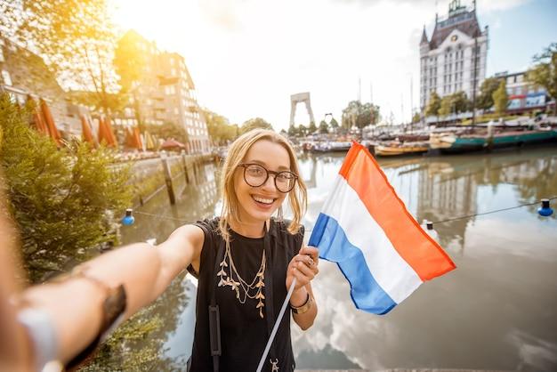 Jonge vrouwentoerist die selfie foto met nederlandse vlag maken die zich bij de oude haven in de stad van rotterdam bevinden