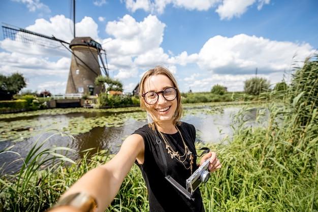 Jonge vrouwentoerist die selfiefoto maken op de mooie landschapsachtergrond met oude windmolens in nederland