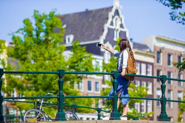 Jonge vrouwentoerist die zelfportret selfie foto op de reis van europa in de stad van amsterdam nemen
