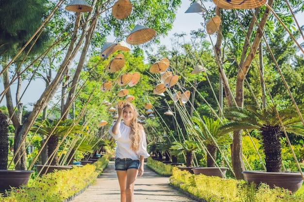 Jonge vrouwentoerist en vietnamese hoeden reizen rond het concept van vietnam