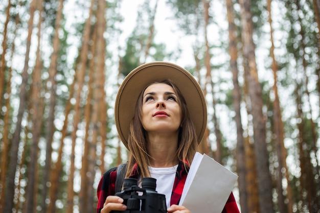 Jonge vrouwentoerist in een hoed, houdt het rode plaidoverhemd een kaart en een verrekijker in het bos.
