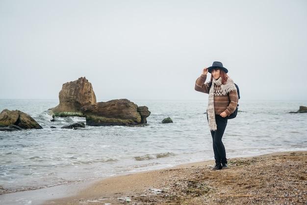 Jonge vrouwentoerist in hoed en met rugzak op strand op een achtergrond van zee en rotsen