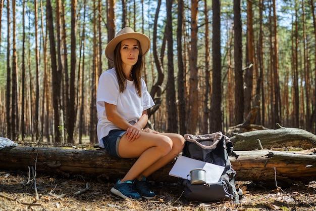 Jonge vrouwentoerist in hoed en t-shirt zit op een logboek tijdens een stop in het bos.