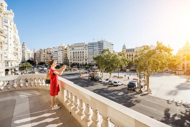 Jonge vrouwentoerist in rode jurk die het ayuntamiento-plein fotografeert vanaf het terras van het stadhuisgebouw in valencia tijdens het ochtendlicht in spanje