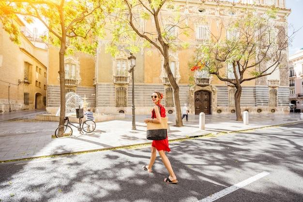 Jonge vrouwentoerist in rode kleding die de straat in de oude stad van de stad valencia, spanje loopt