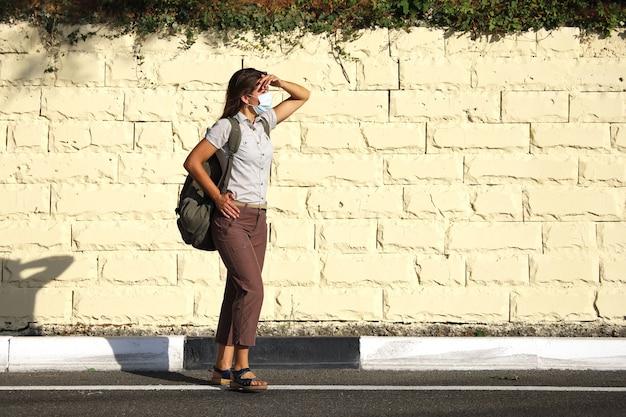 Jonge vrouwentoerist staat aan de kant van de weg met turen in de verte