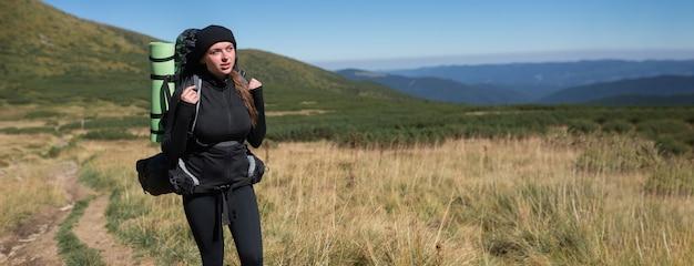 Jonge vrouwentoerist staat op een berghelling
