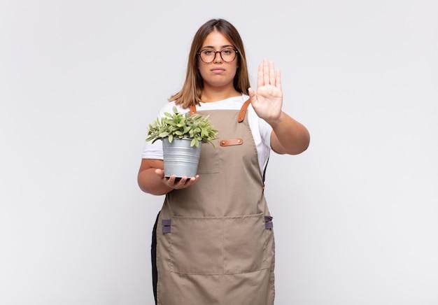 Jonge vrouwentuinman die ernstig, streng, ontevreden en boos kijkt die open palm toont die stopgebaar maakt