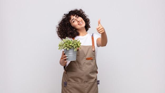 Jonge vrouwentuinman die zich trots, zorgeloos, zelfverzekerd en gelukkig voelt, positief glimlacht met omhoog duimen