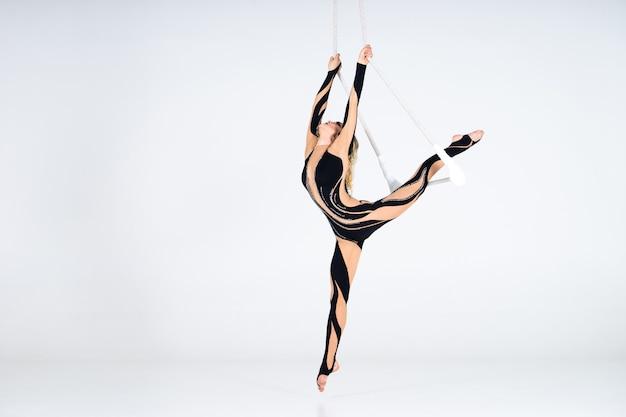 Jonge vrouwenturner die zwart kostuum op trapeze op wit draagt.