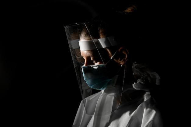 Jonge vrouwenverpleegster die in medisch masker en het beschermende scherm neer in donkere ruimte kijken.