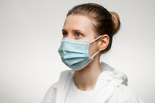 Jonge vrouwenverpleegster die in medisch masker opzij kijken.
