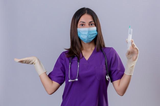 Jonge vrouwenverpleegster die medische uniforme beschermend maskerhandschoenen draagt en met de spuit van de stethoscoopholding geen idee en verward kijkt die zich met opgeheven wapen bevindt