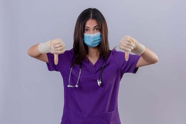 Jonge vrouwenverpleegster die medische uniforme beschermend maskerhandschoenen draagt en met een stethoscoop die duimen toont