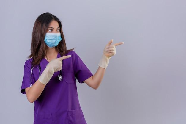Jonge vrouwenverpleegster die medische uniforme beschermend maskerhandschoenen draagt en met stethoscoop met twee handen en vingers aan de kant richt
