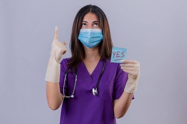 Jonge vrouwenverpleegster die medische uniforme beschermende maskerhandschoenen draagt en met de herinneringsdocument van de stethoscoopholding met ja woord dat met omhoog vinger richt