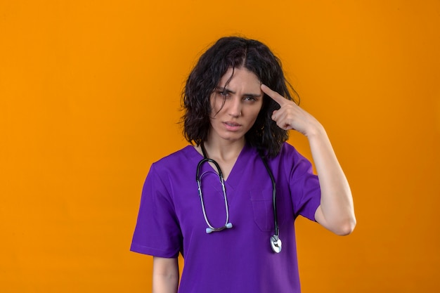 Jonge vrouwenverpleegster in medisch uniform en met stethoscoop die tempel met vinger richt die zich hard op een idee met een serieuze blik concentreren