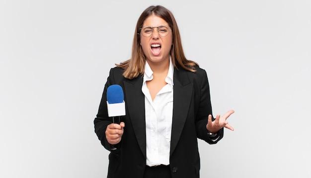 Jonge vrouwenverslaggever die boos, geïrriteerd en gefrustreerd schreeuwend kijkt
