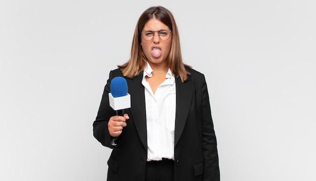Jonge vrouwenverslaggever die walgt en geïrriteerd voelt, tong uitsteekt, niet van iets smerigs en vies houdt