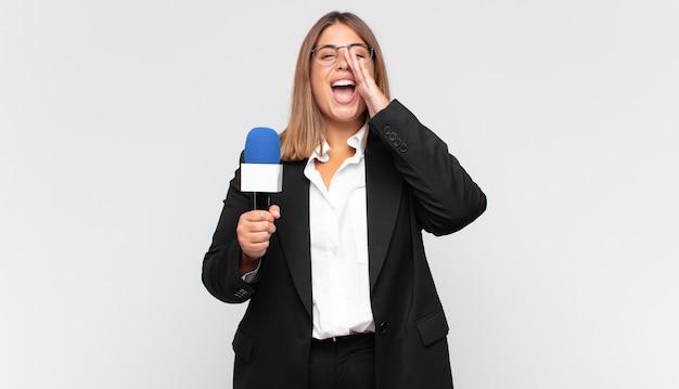 Jonge vrouwenverslaggever die zich gelukkig, opgewonden en positief voelt, een grote schreeuw geeft met handen naast de mond, roept