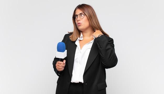 Jonge vrouwenverslaggever die zich gestrest, angstig, moe en gefrustreerd voelt, de hals van het shirt trekt, gefrustreerd kijkt door het probleem