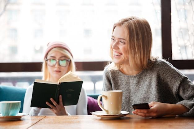 Jonge vrouwenvrienden die boek lezen en koffie drinken.