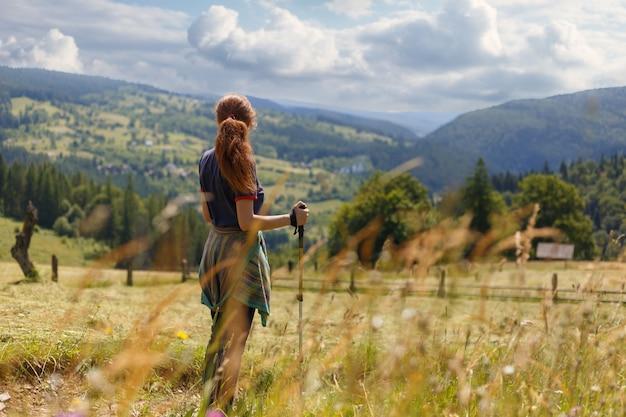Jonge vrouwenwandelaar die bewonderend een bergmening bevinden die uit over verre waaiers van bergen en valleien kijken