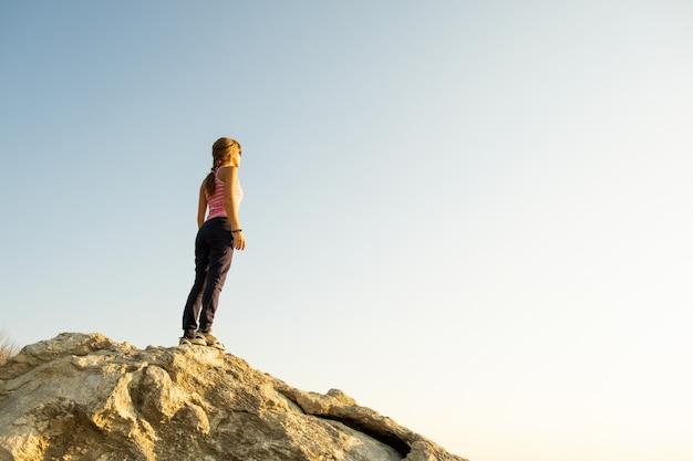 Jonge vrouwenwandelaar die zich alleen op grote steen in ochtendbergen bevinden