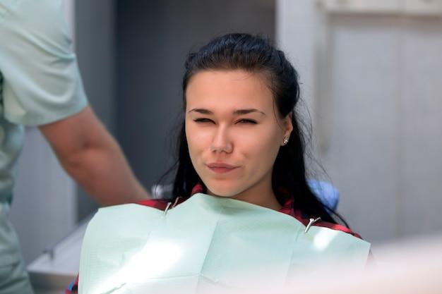 Jonge vrouwenzitting bij de tandarts terwijl het bouwen van een gezicht naar de camera