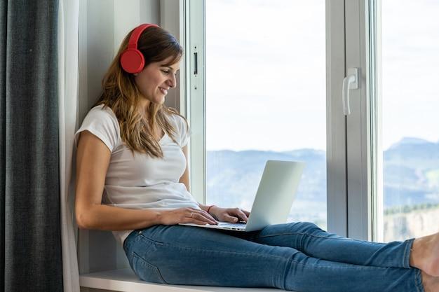 Jonge vrouwenzitting bij haar venster terwijl het luisteren aan muziek en het werken of het bestuderen met haar laptop. concept van nieuwe technologieën en thuis werken.